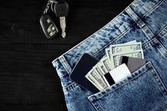 金钱,转账卡和信用卡在蓝色牛仔裤,汽车钥匙的口袋,聪明在与拷贝空间的木背景 库存图片