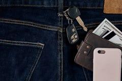 金钱,转账卡和信用卡在蓝色牛仔裤,汽车钥匙的口袋,聪明 顶视图 免版税库存图片