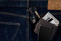 金钱,转账卡和信用卡在蓝色牛仔裤,汽车钥匙的口袋,聪明 顶视图 库存图片