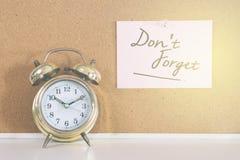 金铃闹钟和书面的笔记唐` T在黄柏板忘记 库存图片