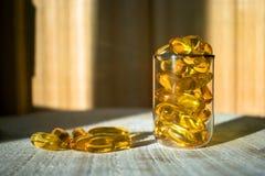金银铜合金油维生素, Ω在一个玻璃烧杯的3个胶囊在t 免版税库存照片