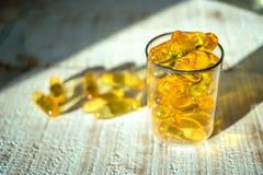 金银铜合金油维生素, Ω在一个玻璃烧杯的3个胶囊在t 库存照片