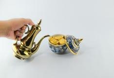 金锭金水罐在Benjarong白色backgr的茶玻璃 库存照片