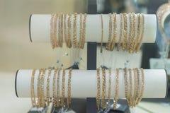 金镯子在一个金银手饰店的橱窗里在金义卖市场 在风的金镯子在商店 免版税库存照片