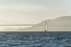 金门大桥在日落风景的航行游艇 免版税库存图片