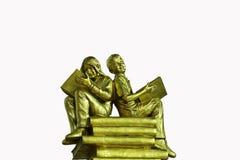 金雕象男孩和女孩读了一本书 免版税库存照片