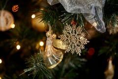 金雪花和一个天使在圣诞树分支 免版税库存照片