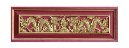 金黄伙伴龙木雕刻的sclupture在花中和绘在白色背景隔绝的红色木盘子 库存图片