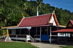 金黄佛教寺庙的红色屋顶在一个小泰国村庄的密林 库存图片