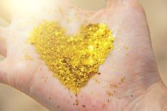 金黄光亮的心脏在女孩的手上在 在t的心脏 免版税图库摄影