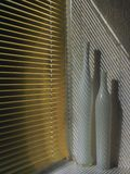 金黄半开放窗帘在白色墙壁上的被投下的倾斜的平行的阴影,两个高白色花瓶在基石站立 库存图片