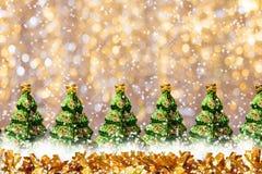 金黄发光的玻璃玩具闪亮金属片和行绿化在金黄bokeh背景的圣诞树与雪的并且复制空间 图库摄影
