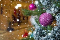 金黄和桃红色中看不中用的物品的特写镜头图象在圣诞树的在灼烧的壁炉前面 背景美好的圣诞节 库存图片