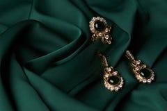 金黄圆环和对有绿色绿宝石和金刚石的耳环 图库摄影