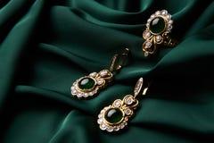 金黄圆环和对有绿色绿宝石和金刚石的耳环 库存图片