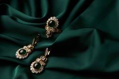 金黄圆环和对有绿色绿宝石和金刚石的耳环 免版税库存图片