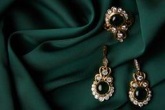 金黄圆环和对有绿色绿宝石和金刚石的耳环 库存照片