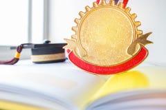 金黄奖牌和毕业盖帽在书,毕业生教育 免版税图库摄影