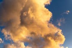 金黄小时云彩有深刻的蓝色背景 免版税库存图片