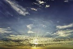 金黄小时太阳通过在橙色蓝天的美好的低白色疏散云彩发出光线 免版税库存图片