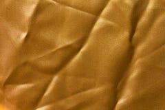 金黄布料纹理与折叠的。 免版税库存图片