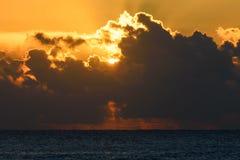 金黄日出或日落在海 发光通过云彩的太阳的光芒 库存照片