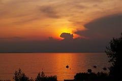 金黄日落天空和水在湖加尔达 免版税图库摄影