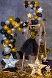 金黄晚礼服的装饰与垂悬在俱乐部演播室装饰的木挂衣架的皮夹克的 免版税库存图片