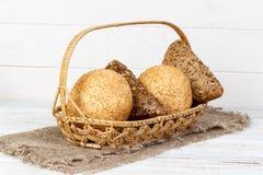 金黄棕色坚硬生了酒垢的小圆面包一个新鲜的篮子  射击在空白背景 图库摄影