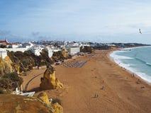 金黄沙子海滩在有peaples sunbeds的阿尔布费拉葡萄牙和 图库摄影