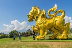 金黄狮子雕象商标在蓝天和白色下覆盖backgrou 免版税库存照片