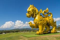 金黄狮子雕象商标在蓝天和白色下覆盖backgrou 免版税图库摄影