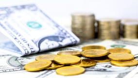 金黄硬币堆和在白色桌backgro的美元钞票 免版税图库摄影