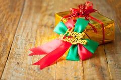 金黄礼物盒和红色丝带和新年好礼物在木头b 免版税库存图片