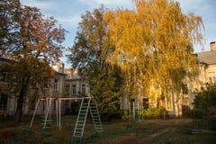 金黄秋天树和操场在老房子的庭院里 沃罗涅日,俄罗斯 库存图片