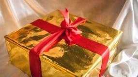 金黄箱子与红色丝带的礼物 免版税库存图片