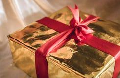 金黄箱子与红色丝带的礼物 免版税库存照片