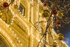 金黄红色球明亮的装饰在反对装饰的黄色大厦背景的一个欢乐冬天晚上 库存照片