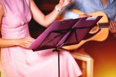 金黄蓝色 弹吉他,木墙壁背景,电或者声学吉他的歌手独奏声音妇女的人的男性手 图库摄影