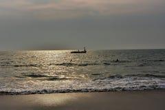 金黄阳光的折射的看法在海海滩的与小船的剪影创造了不可思议的背景 免版税库存照片
