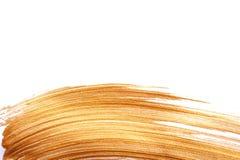 金黄颜色油漆污迹刷子冲程 油漆飞溅线 在白色背景的摘要形状丙烯酸酯的油金子与 图库摄影