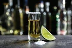 金黄龙舌兰酒射击了与水多的石灰和盐 库存照片