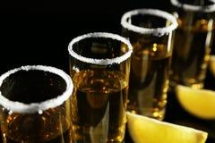 金黄龙舌兰酒射击行与水多的石灰的楔住 免版税库存照片