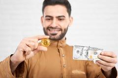 金黄bitcoin与它比较了相当一百美元价值 免版税库存图片