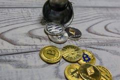 金黄bitcoin和其他隐藏货币在下落的玩具金属化桶特写镜头 图库摄影