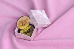 金黄bitcoin在有一把小弓的一个小桃红色礼物盒在毯子由软和蓬松浅粉红色的羊毛织品wi做成 库存图片