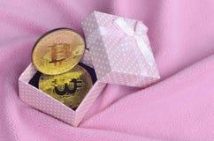 金黄bitcoin在有一把小弓的一个小桃红色礼物盒在毯子由软和蓬松浅粉红色的羊毛织品wi做成 免版税库存照片