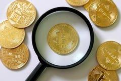 金黄Bitcoin复制品和放大镜在白色木背景 企业和财务概念 免版税库存图片