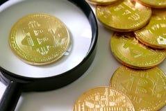 金黄Bitcoin复制品和放大镜在白色木背景 企业和财务概念 库存照片