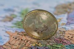 金黄Bitcoin硬币关闭有欧洲地图被弄脏的背景  库存图片